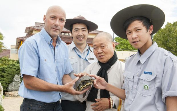 Department of Agriculture and Food officer Glen Coupar with Minh Le, Venerable Thich Phuoc Nhon and Tuan Huang, of the Pho Quang Temple with a  red-eared slider turtle.