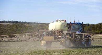 Boom spray applying chemical over pasture paddock