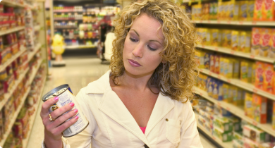 Customer reading a food label while shopping in supermarket.