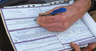 A producer is filling out a National Vendor Declaration (NVD) waybill to send his sheep to the abattoir.