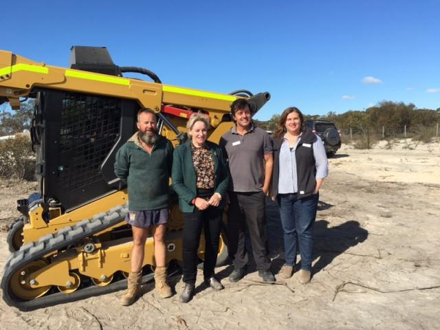 A team of DPIRD staff responsible for managing construction of the State Barrier Fence Esperance extension, with the Minister for Agriculture and Food, in front of a bobcat.