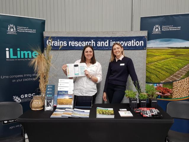 Two women standing at a DPIRD grains research display at the Albany Show