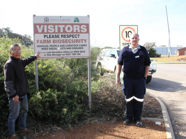 "Two men standing with an example of farm entry signage that states ""Visitors, please respect farm biosecurity"""