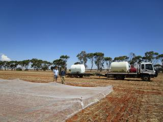Two men in a trial paddock with a mobile irrigation unit behind.