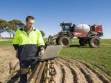 Farmer looking at laptop on SP sprayer