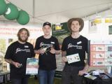 3 men in MyPestGuide uniform standing in front of festival display