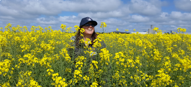 DPIRD crop production agronomist standing in tall canola crop