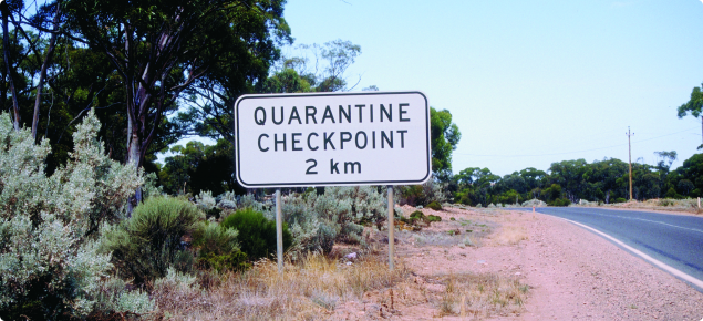White sign with the words quarantine checkpoint 2km written in black. This sign is on the left hand side of a road.