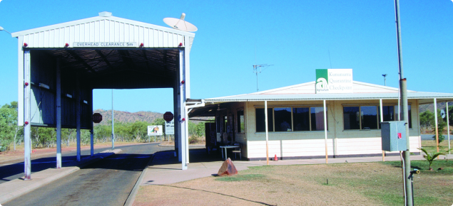 The Kununurra quarantine checkpoint, a white building alongside a large, tall, open backed shed used for inspections.