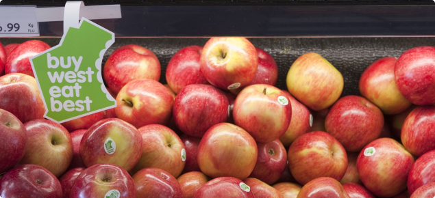 Sundowner™ apples on a supermarket shelf with a Buy West Eat Best campaign label hanging above..