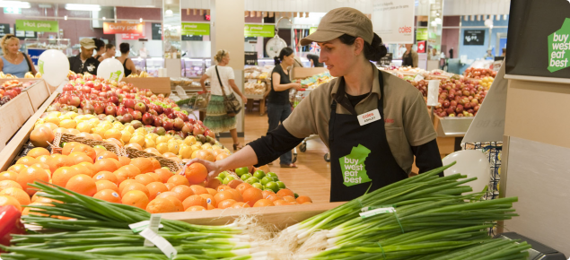 Supermarket assistant with Buy West Eat Best logo on her apron.