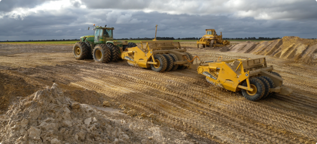 Carry graders excavating a pit for clay spreading