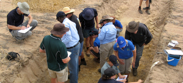 Photograph of people describing the soil in a soil pit