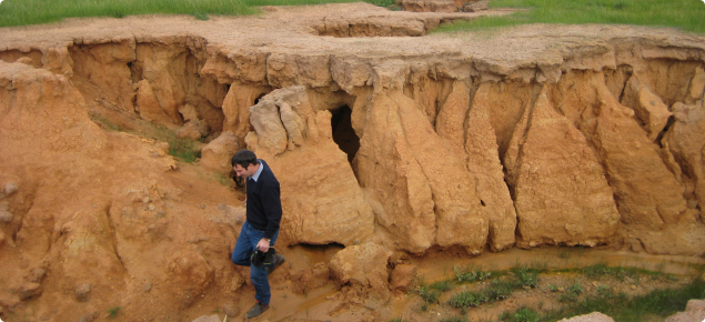 Photograph of severe gully erosion with person standing in the gully