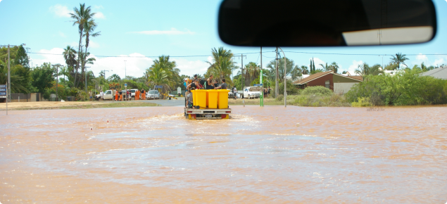 View from a vehicle driving through flood waters in a country town