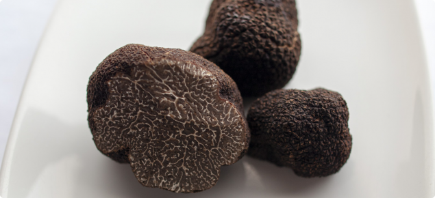 The external surface of the black truffle is rough and pebbly, the internal is blackish with white veins