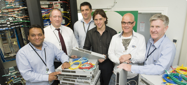 DAFWA IT infrastructure staff in server room with stack of IT network equipment.