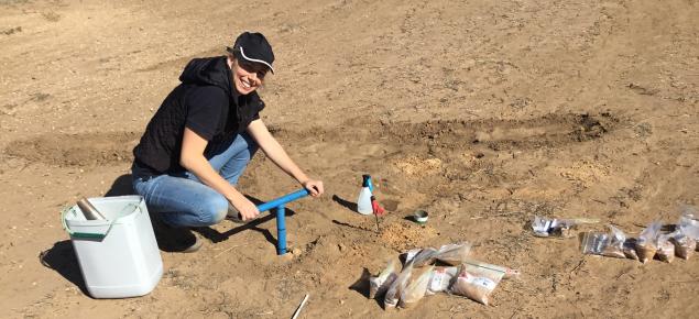 Person soil sampling in bare paddock