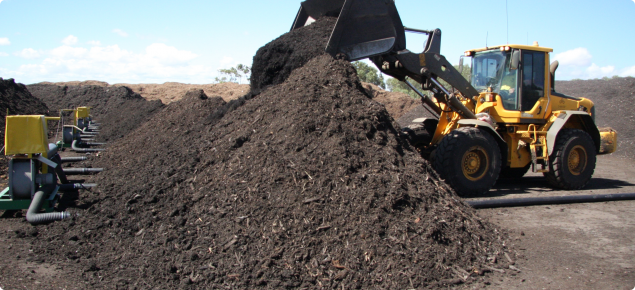 Front end loader piling partly composted material onto aeration pipes