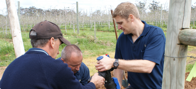 Three members of the demo set up team complete setting up the irrigation pipingsub-main