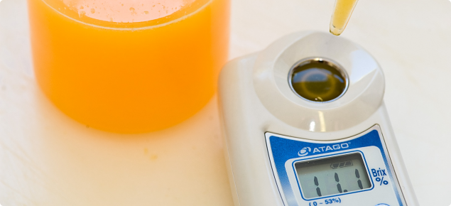 Digital refractometer measuring percentage Total Soluble Solids of citrus juice