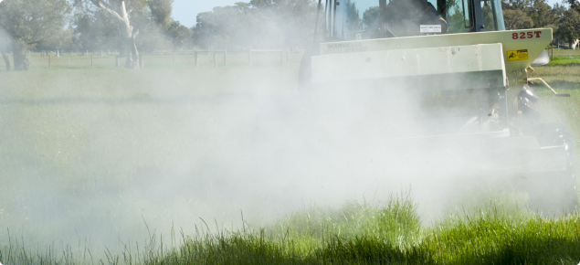 photo showing spreading of fertiliser from the back of a trailer attached to a tractor onto pasture