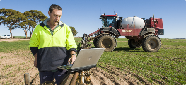 Farmer looking at laptop on SP sprayer
