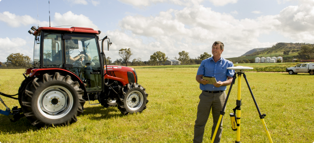 Research officer in fiield with GPS equipment next to tractor.