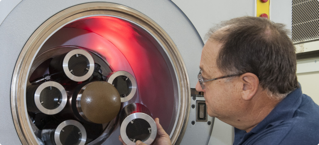 Placing a cannister containing fruit fly pupae in the X-Ray irradiator