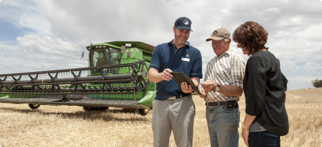 Department of Agriculture and Food Western Australia's Christiaan Valentine stnding in front of a harvester showing farmers how to access DAFWA's website on an iPad