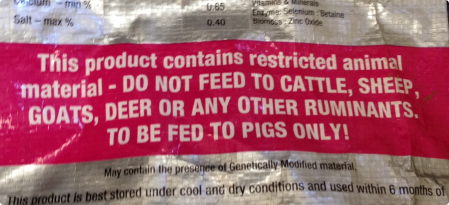 Bag of pig feed labelled with a statement indicating the feed contains restricted animal material.