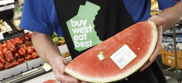 Greengrocer holding a sliced watermelon with Buy West Eat Best logo visible on packaging.