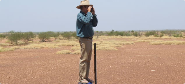 Photograph of rangeland station manager taking a photo on a monitoring site
