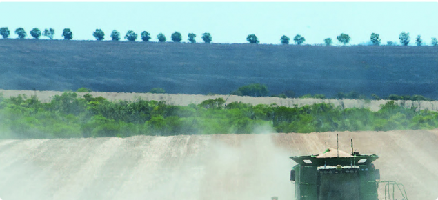 Two harvesters in a field with a tree line behind them.