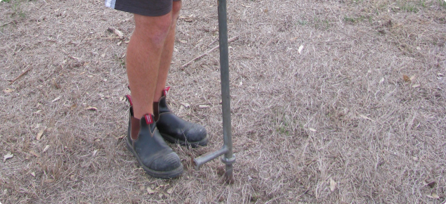 Photograph of a person leaning on a manual pogo stick soil sampler