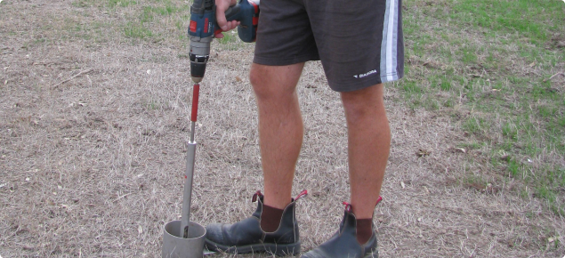 Photograph of a hand-held drill-powered soil sampler