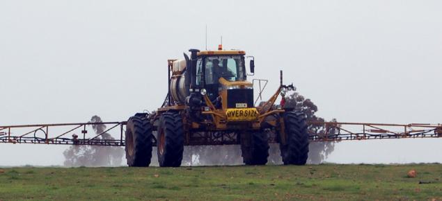 Ground rig spraying chemical onto pasture