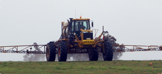 Ground rig spraying chemical onto pasture