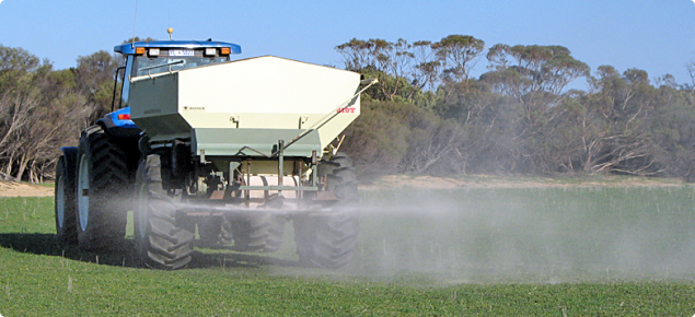 Agricultural lime being spread on a pasture in spring, a good option to spread the workload