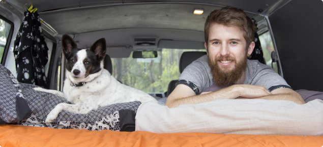 man in campervan with dog