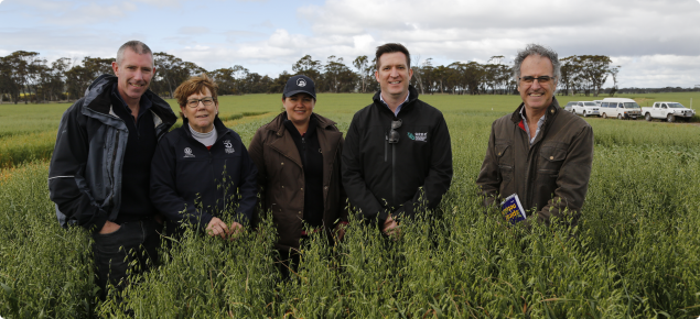 Group of five people standing in an oats paddock on a cold day.