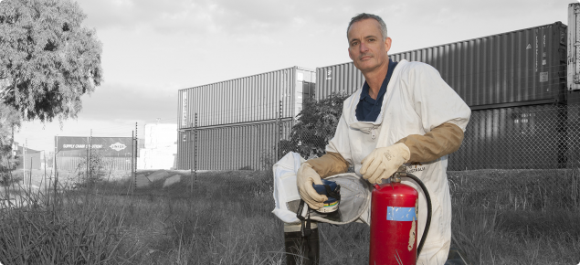DAFWA Senior Technical Officer Marc Widmer in a protective suit, prepares to spray near shipping containers at the interstate railway terminal at Kewdale–Welshpool where many European wasp nests have been discovered.