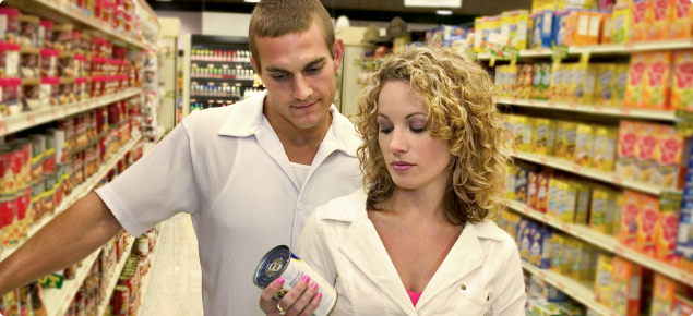 Customers reading a food label while shopping in a supermarket