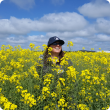 DPIRD regional agronomist standing in tall canola crop