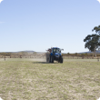A boom spray in use, spraying a paddock before seeding