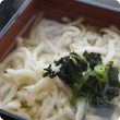Bowl of Japanese noodle soup showing a close up of the thick white noodles sitting in clear soup with a green leafy vegetable garnish on top.
