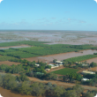 Vast flooding of Carnarvon horticultural area with brown muddy water spanning into the distance