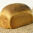 A loaf of bread made with lupin flour, sitting on a bed of Australian sweet lupin seed.