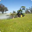 Using a tractor to spread fertiliser on pasture
