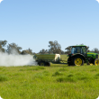 Fertiliser being spread on pasture from the trailer of a tractor - side view